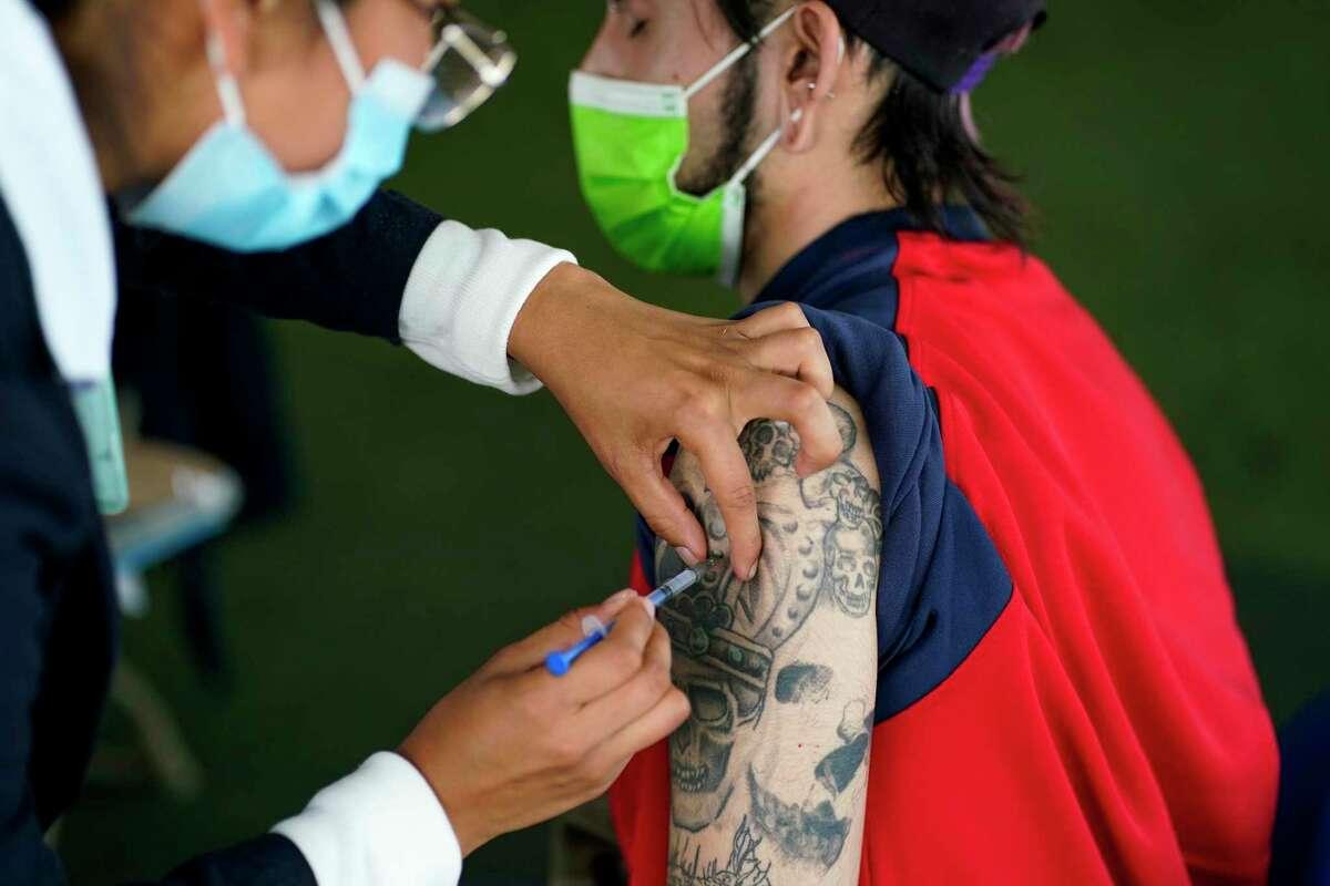 Una trabajadora de salud administra una dosis de la vacuna de Pfizer contra el COVID-19 durante la campaña de vacunación para personas de 18 a 29 años, el jueves 19 de agosto de 2021, en la Ciudad de México.