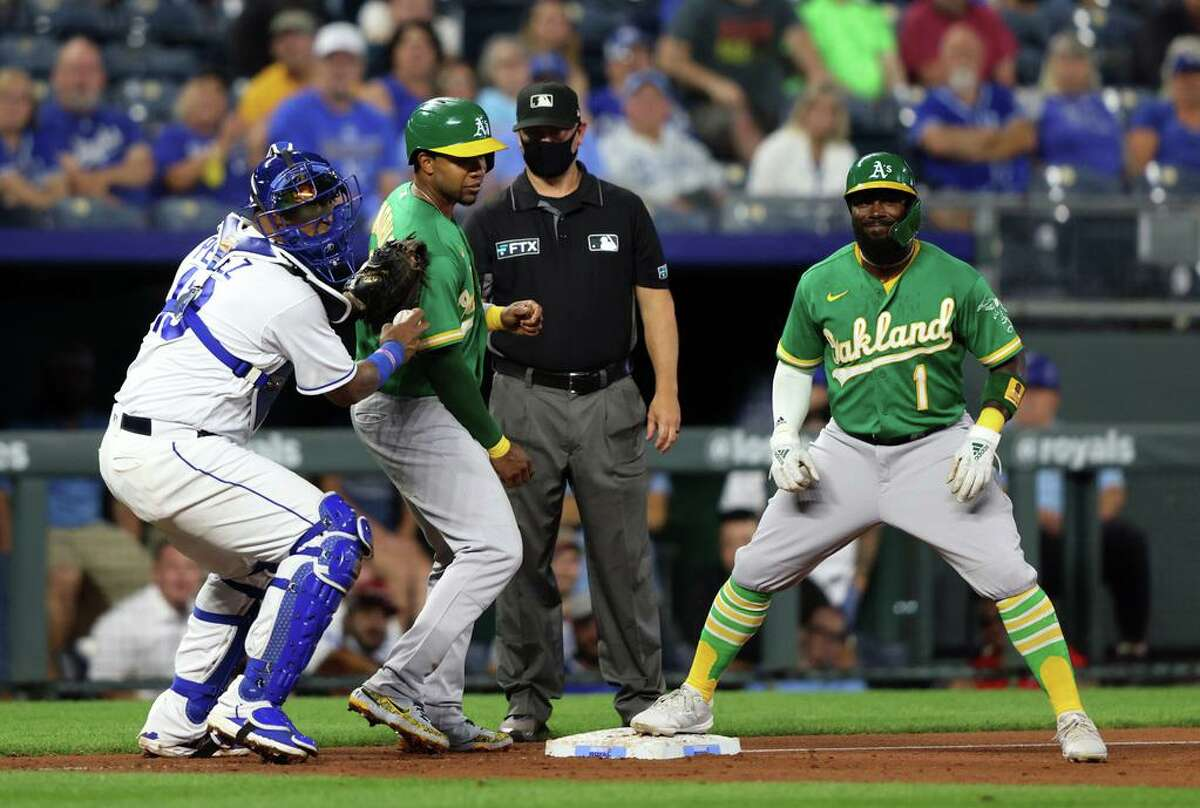 KANSAS CITY, MISSOURI - SEPTEMBER 14: Elvis Andrus #17 of the Oakland Athletics is tagged out by Salvador Perez #13 of the Kansas City Royals at third base after being caught in a rundown during the 2nd inning of the game at Kauffman Stadium on September 14, 2021 in Kansas City, Missouri. (Photo by Jamie Squire/Getty Images)