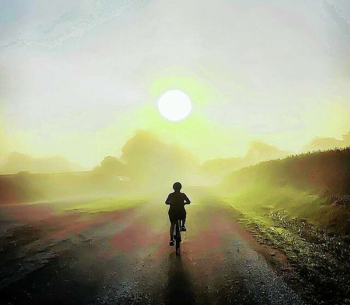 A lone bicyclist takes an early morning journey along a country road in Morgan County.