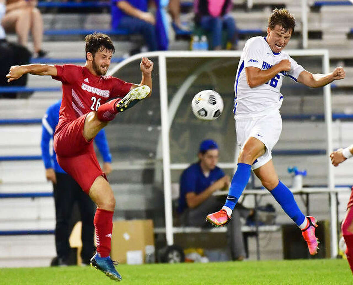 SIUE's Corban McAvinew volleys a shot past Saint Louis University's Seth Anderson in the second half of Tuesday night's Bronze Boot game against Saint Louis University at Hermann Stadium in St. Louis. The teams played to a 1-1 tie.