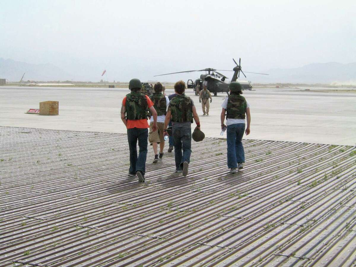 """Members of the band Edisun prepare to board a chopper in Baghram, Afghanistan during one of their many concert tours in the Middle East. The band is the subject of a new documentary, """"Bulletproof Wings,"""" now streaming on Tubi."""