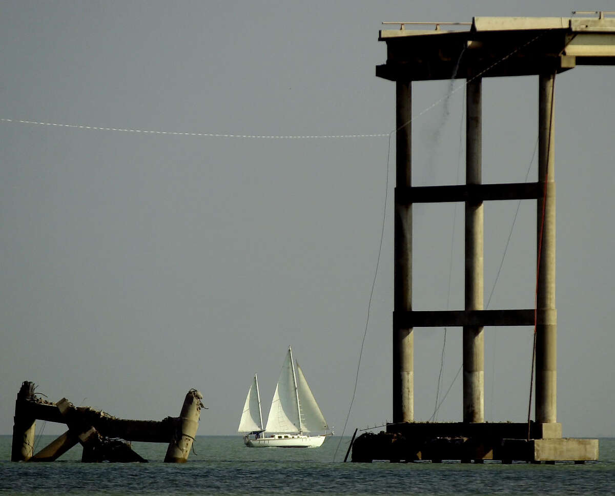 A sailboat passes a collapsed section of the Queen Isabella Causeway in Port Isabel, Texas, Sunday, Sept. 16, 2001.