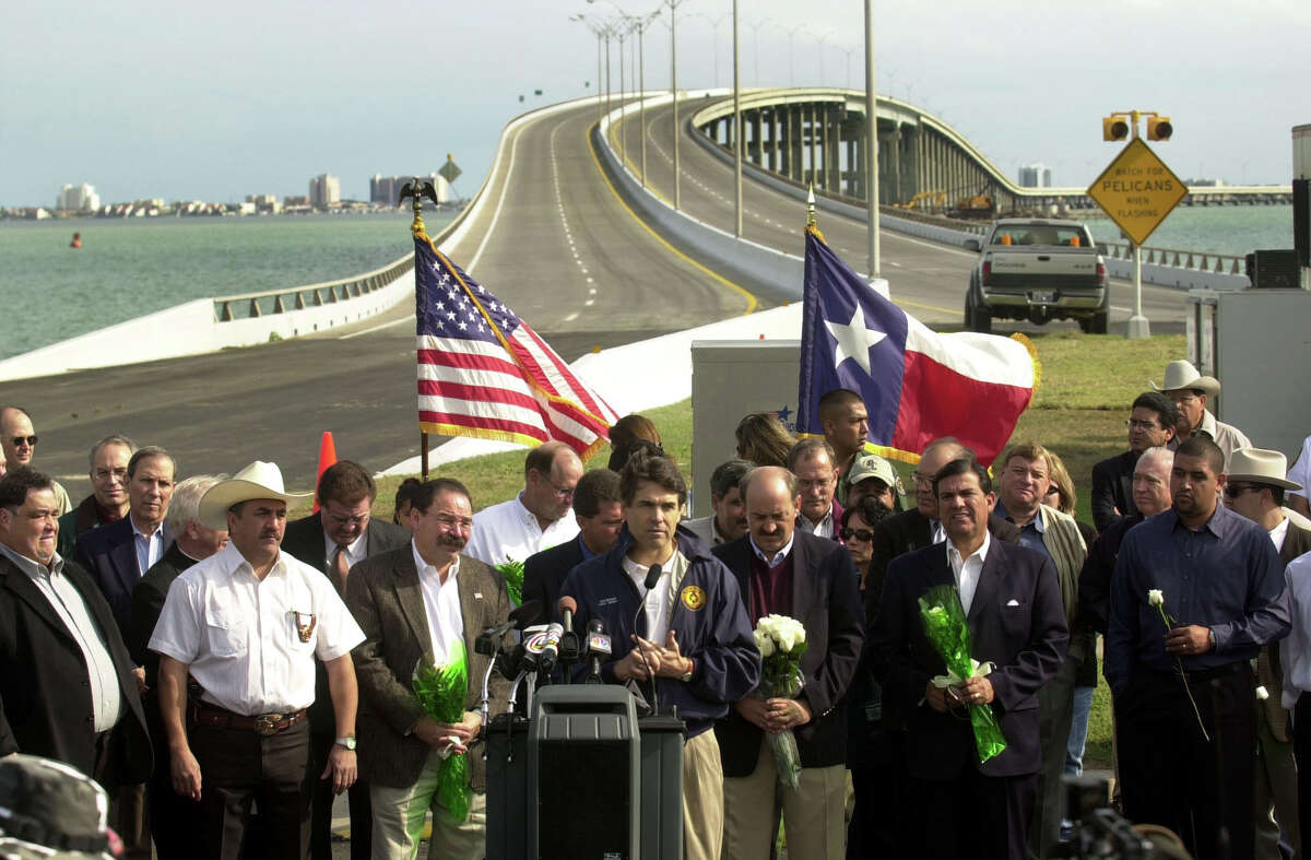 Texas Gov. Rick Perry speaks at the dedication ceremony of the opening of the Queen Isabella Causeway on Wednesday, Nov. 21, 2001. The causeway was repaired in just over two months after a string of barges hit it, causing a partial collapse that took eight lives on Sept. 15. South Padre Island is visible in the background.