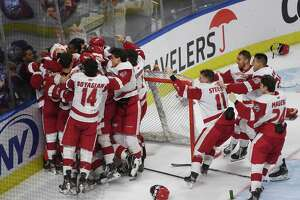 Sacred Heart teammates mob goalie Josh Benson following their team's 4-1 victory over Quinnipiac in the championship game of the Connecticut Ice college hockey tournament at the Webster Bank Arena in Bridgeport, Conn. on Sunday January 26, 2020.