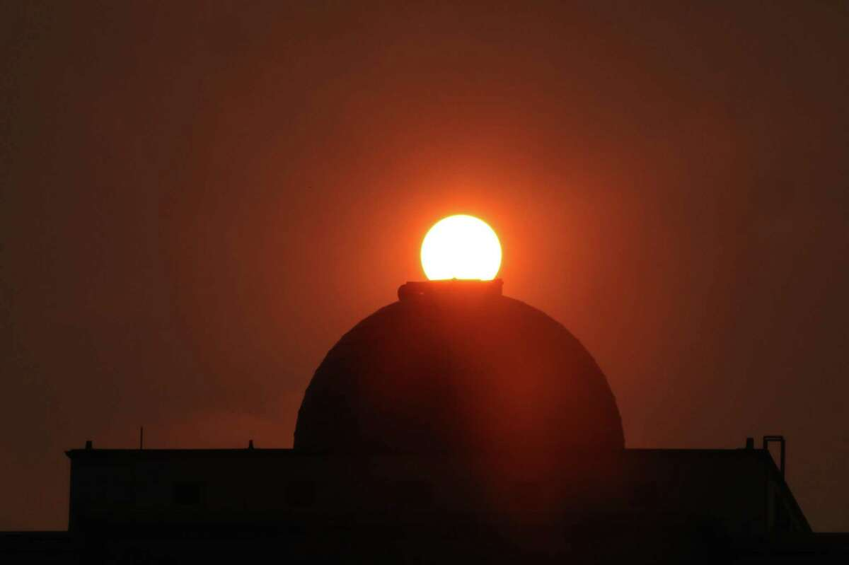 The sun is seen rising over the dome atop the Science Hall at City College of San Francisco in San Francisco , Calif. Smoke from the wildfires has affected the air quality in the Bay Area.