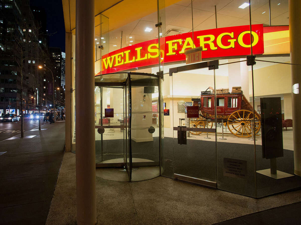 A 2014 files photo showing pedestrians as they pass in front of a Wells Fargo & Co. bank branch in New York.