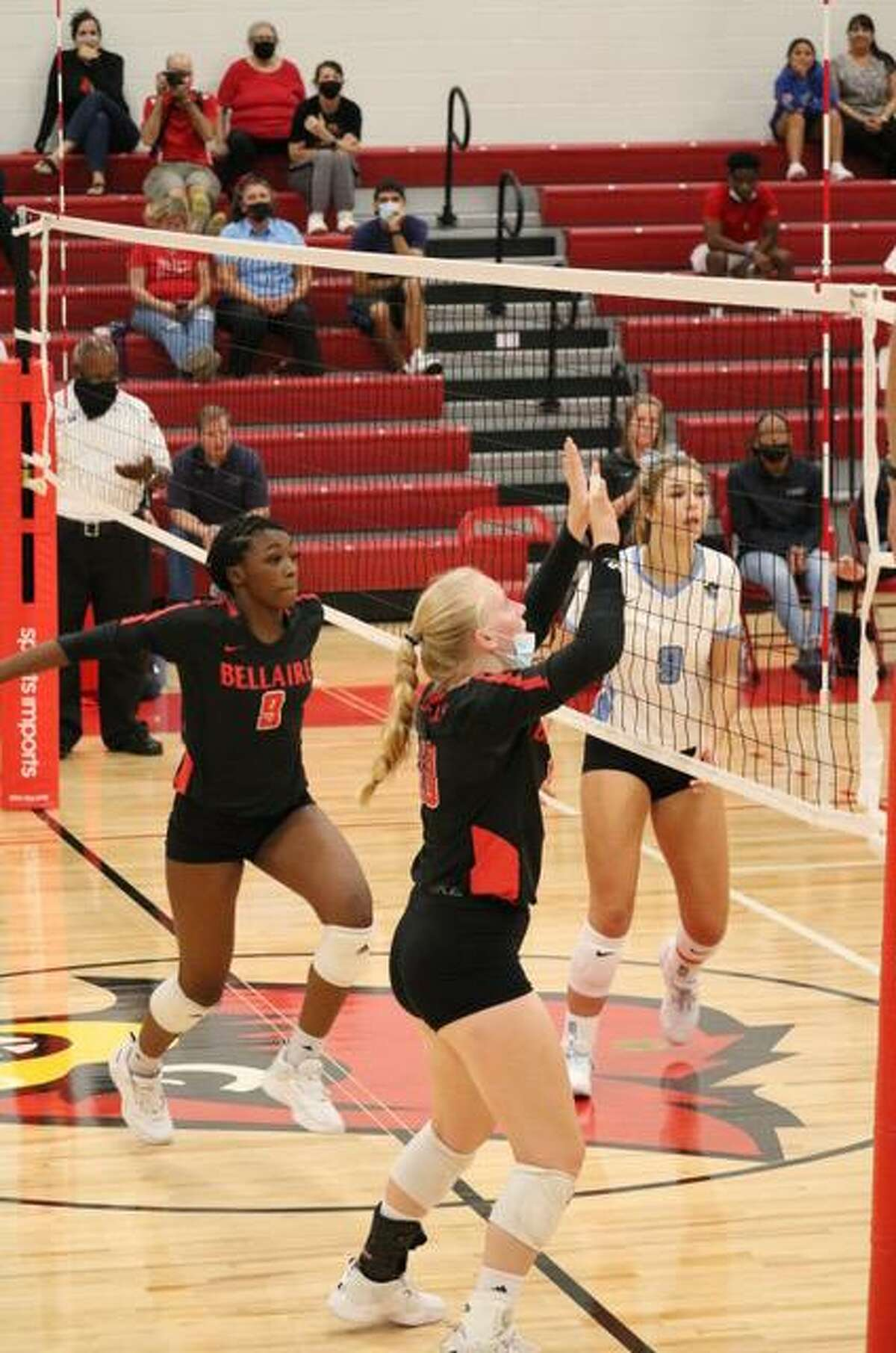 Bellaire volleyball middle hitter Paris Gilmore (left in black) and setter Adeline Lasics (right in black) during a point in the Lady Cardinal's match against Brazoswood on Aug. 31.