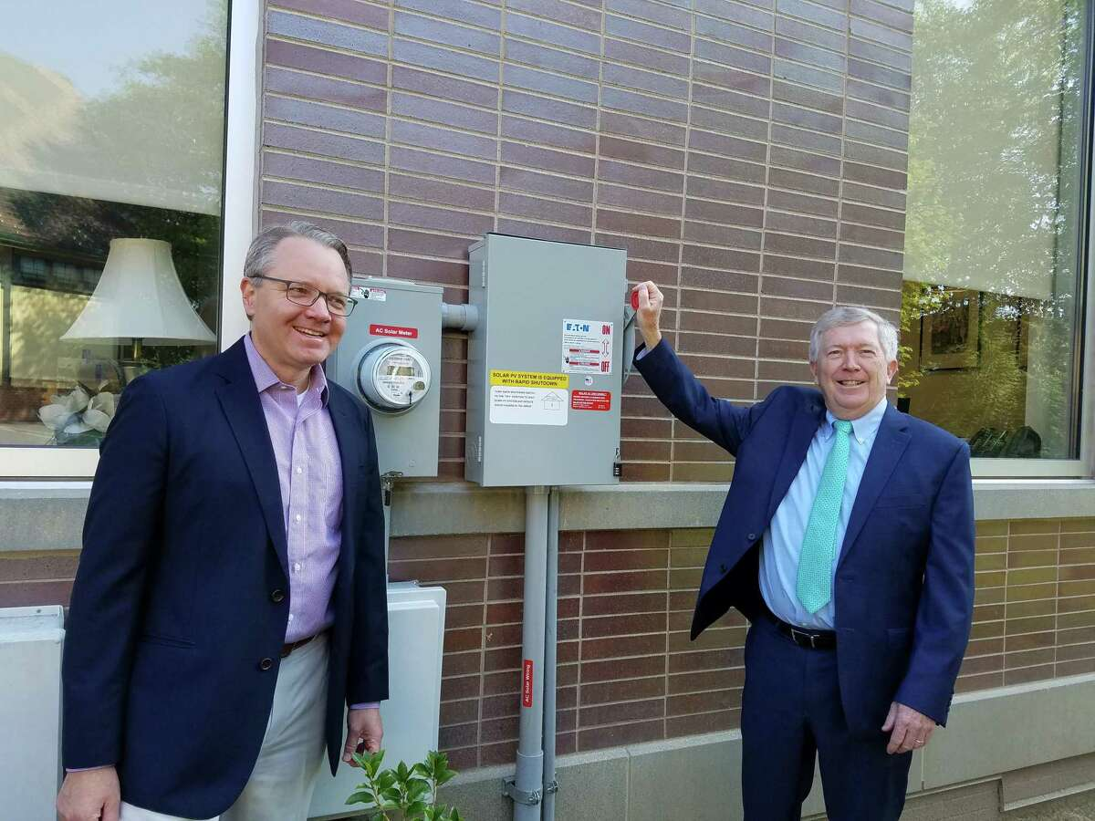 First Selectman Kevin Moynihan raised the lever to turn on the 128 solar panels on the roof of New Canaan Town Hall last year. Next to him is Mark Robbins of MHR Development, LLC