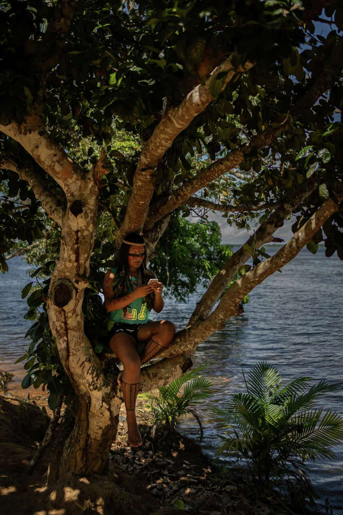 Maira Tatuyo, 22, an indigenous digital influencer with more than 5 million TikTok followers, sits in a tree while posting to her profile in Manus, Brazil, on July 10, 2021.