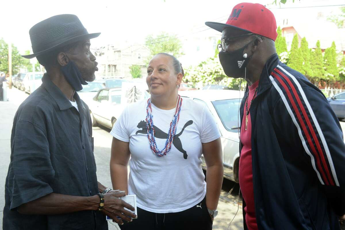City Council member Eneida Martinez stands with fellow councilman Ernie Newton, left, and Henry Webb outside Dunbar School in Bridgeport on Tuesday.