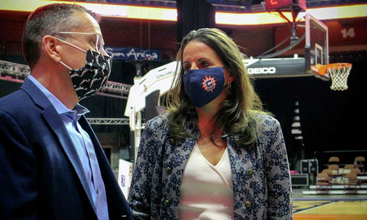 Jennifer Rizzotti, right, speaks with Connecticut Sun head coach Curt Miller, right, following her formal introduction as the new president of the WNBA's Connecticut Sun, Tuesday, April 27, 2021 at the Mohegan Sun Arena in Uncasville, Conn. Rizzotti says she plans to keep her second job this summer as an assistant basketball coach with the United State's women's Olympic basketball team. (AP Photo/Pat Eaton-Robb)