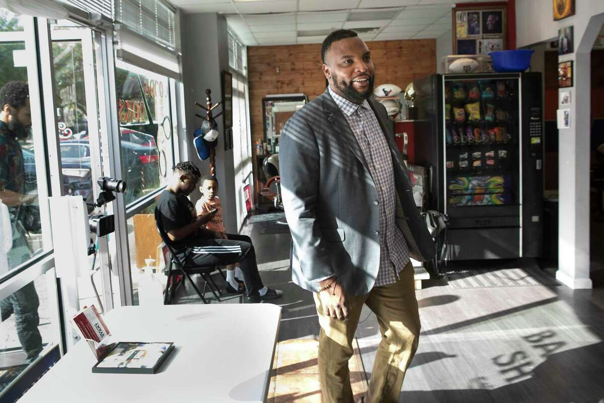Lee Merritt, a Democratic candidate for Texas attorney general, walks into Goode Looks Barber Shop as he campaigns Friday, July 23, 2021 in Houston. Merritt, who lives in the Dallas area, is nationally recognized for his representation of families of Black people killed by police, including serving as co-counsel for George Floyd's family.