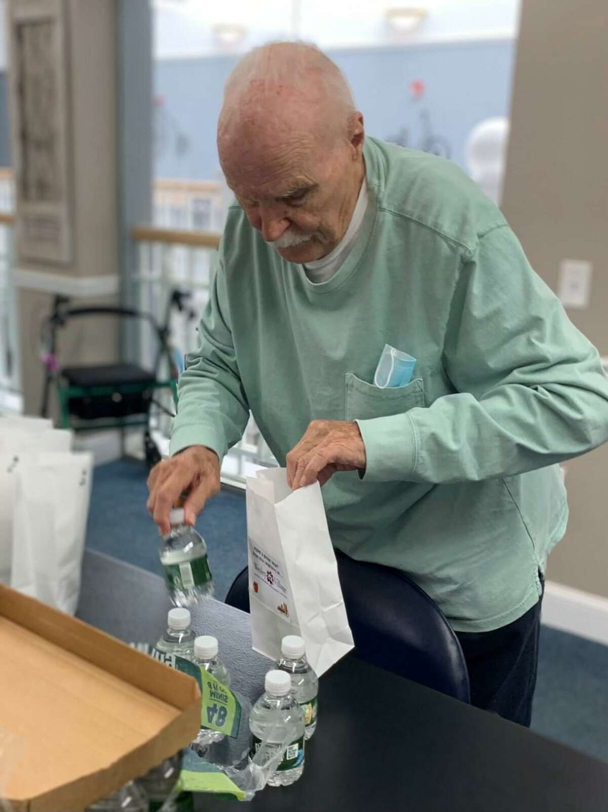 """Crosby Commons resident Frank Dragan packs mini water bottles into """"welcome back"""" bags for Long Hill School staff."""