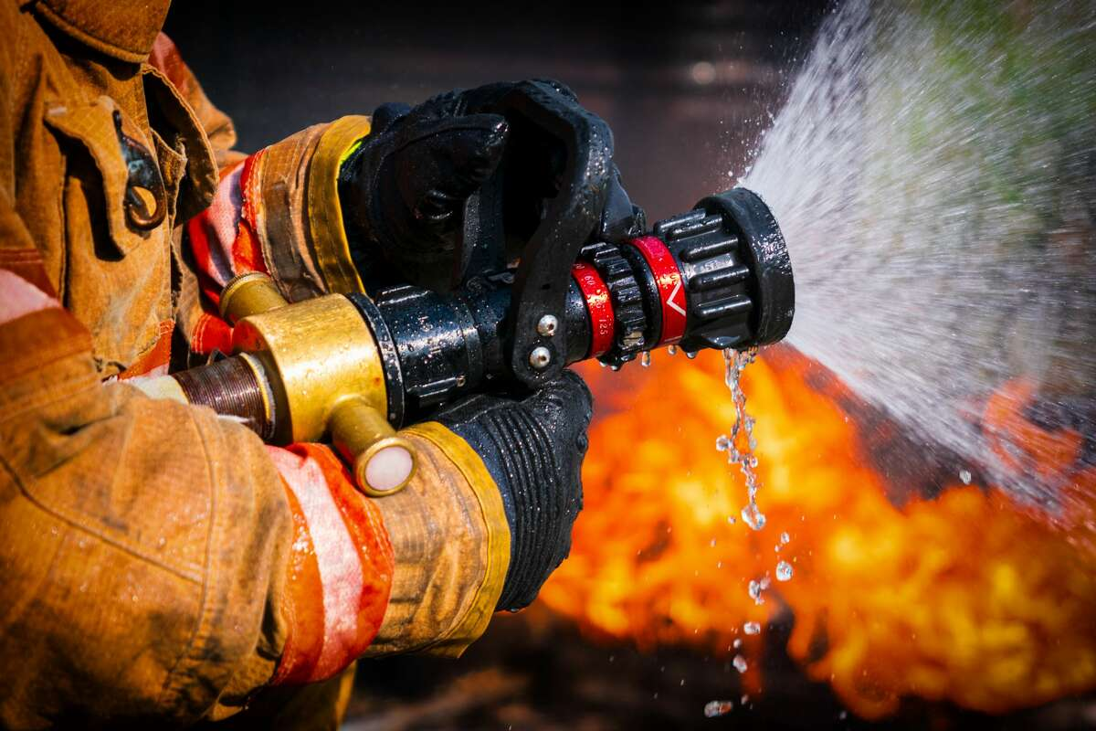 Close-up of firefighter holding a fire hose next to a fire.