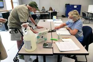 Election official Carol Cipolla, right, checks Tom Cole's ID at the Guilford Fire Department Tuesday during the Republican primary vote for two Board of Education slates.