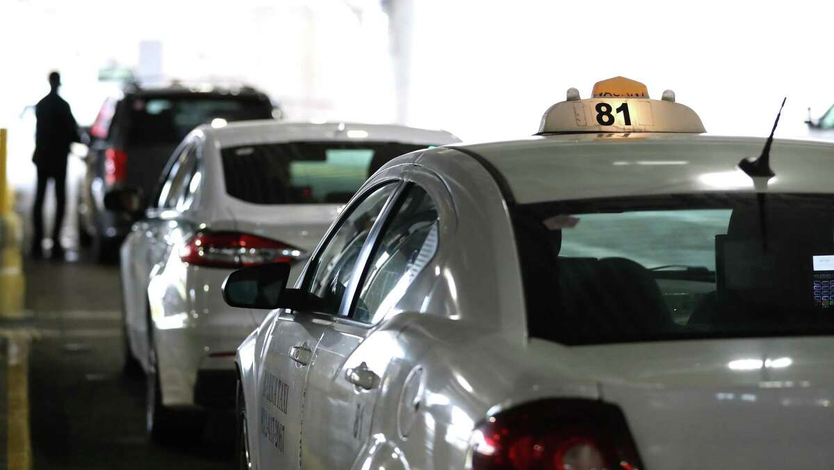 Taxis line up for arriving passengers at Hobby Airport, Wednesday, September 15, 2021, in Houston. The city is rolling back some regulations on taxis, to help them recover from the pandemic and compete with Uber and Lyft.