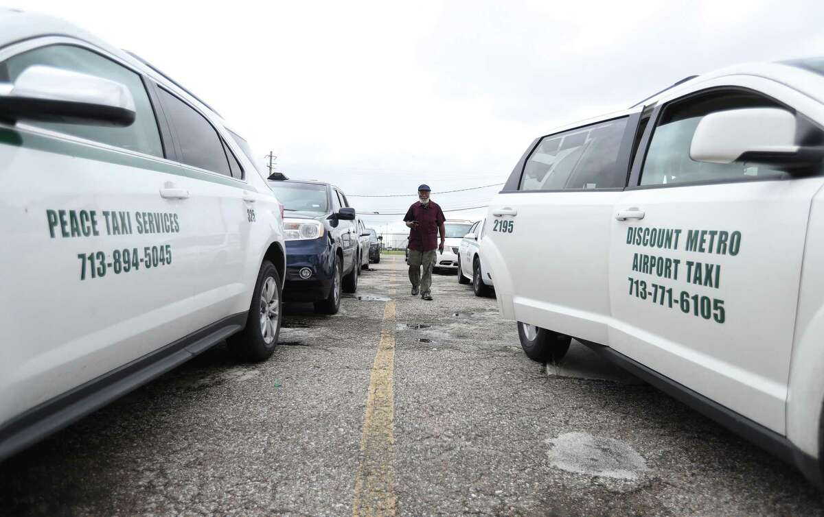 Taxis line up in the staging lot near Hobby Airport, Wednesday, September 15, 2021, in Houston. The city is rolling back some regulations on taxis, to help them recover from the pandemic and compete with Uber and Lyft.