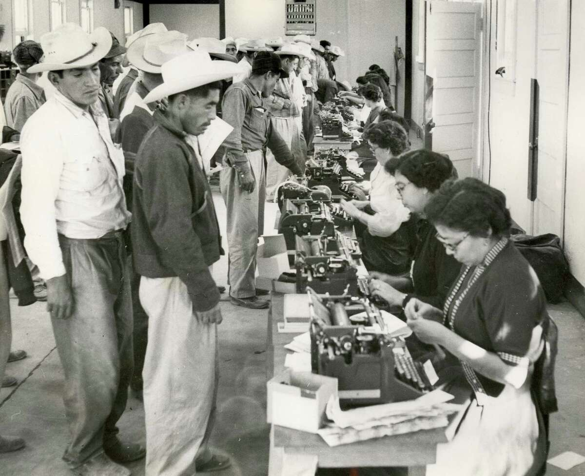Clerks complete short-term labor contracts and create identification cards for workers in the bracero program, which ran from 1942 to 1964.