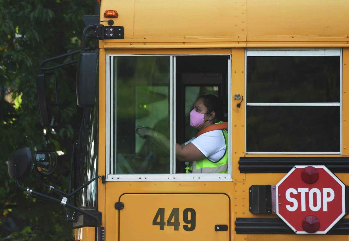 A bus driver wears a mask while driving students on the first day of the 2020-2021 school year at Westover Elementary School in Stamford, Conn. Tuesday, Sept. 8, 2020.