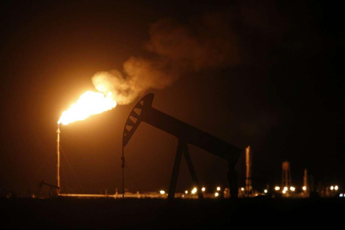 An oil pump jack near a flare at night.