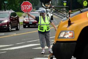 A crossing guard stops traffic on King Street near Naramake, Nathan Hale and Norwalk High Schools, that backs up on Strawberry Hill Wednesday, September 15, 2021, in Norwalk, Conn. Norwalk Public Schools in considering changing start times to ease congestion.