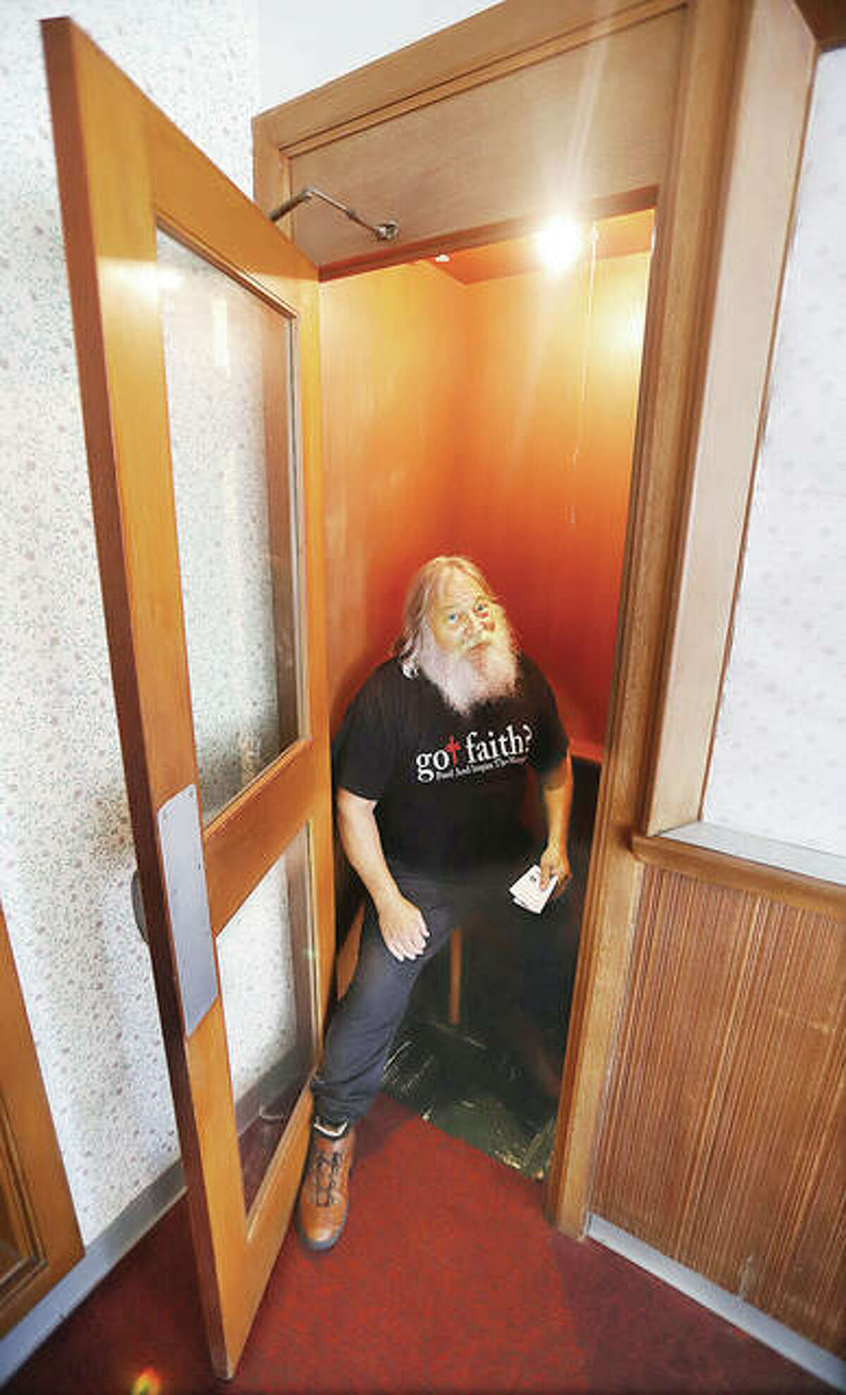 Steve Pegram sits in the built-in phone booth in the corner of lobby of a building donated last week to his ministry. Pegram said people remember the phone booth and ask him if it's still there; it is, but the phone is gone.