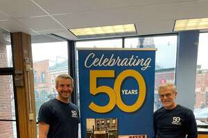 Michael C. Iannuzzi, left, and his father, Michael P. Iannuzzi, stand in front of a sign commemorating the 50th anniversary of the family business, Tyco Printing.