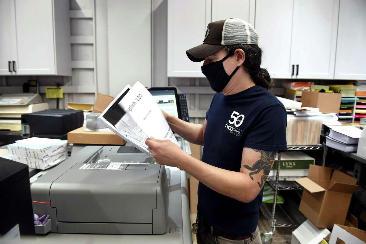 Machine operator Dan Bellucci scans course material at Tyco Printing in New Haven Sept. 9, 2021.