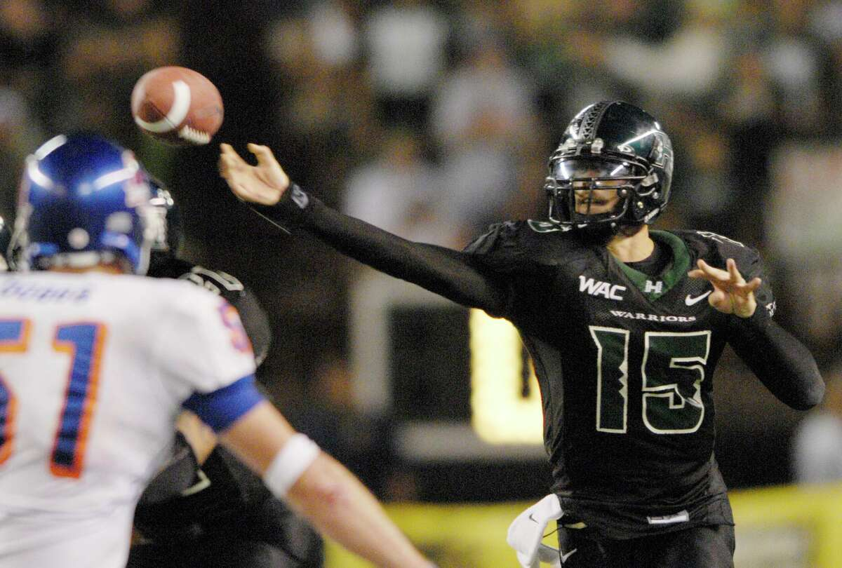 Hawaii quarterback Colt Brennan (15) throws the ball under pressure of Boise State Dallas Dobbs (51) during the fourth quarter of their college football game in Honolulu, Friday, Nov. 23, 2007. (AP Photo/Ronen Zilberman)