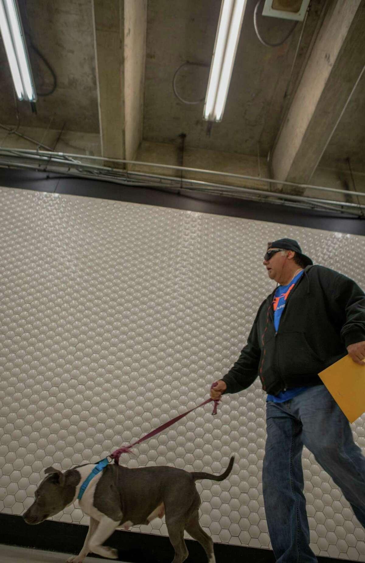 Kenny McKinnon walks his dog, Lola, through BART's Powell station on Friday, Nov. 6, 2015 in San Francisco, Calif.