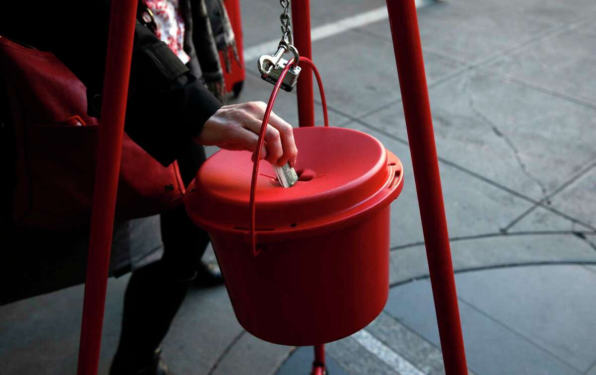 """A file photo of a shopper making a cash Salvation Army donation in San Francisco. With some retailers still feeling the pinch of too few coins in circulation, the nonprofit kicks off its 2021 Connecticut fundraising campaign on Sept. 16, 2021, with plans to highlight payment card scanners, """"virtual red kettles"""" and other alternatives to make donations this holiday season."""