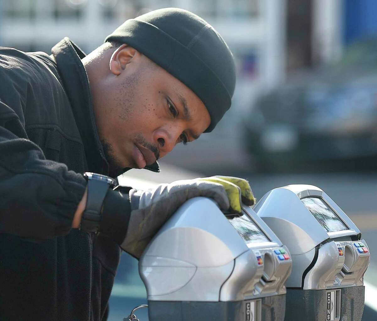 A technician works on a credit-card-enabled parking meter in 2019 in Stamford, Conn. Some retailers continue to warn customers they are short on coins in their tills to make change, asking them to use payment cards if possible.