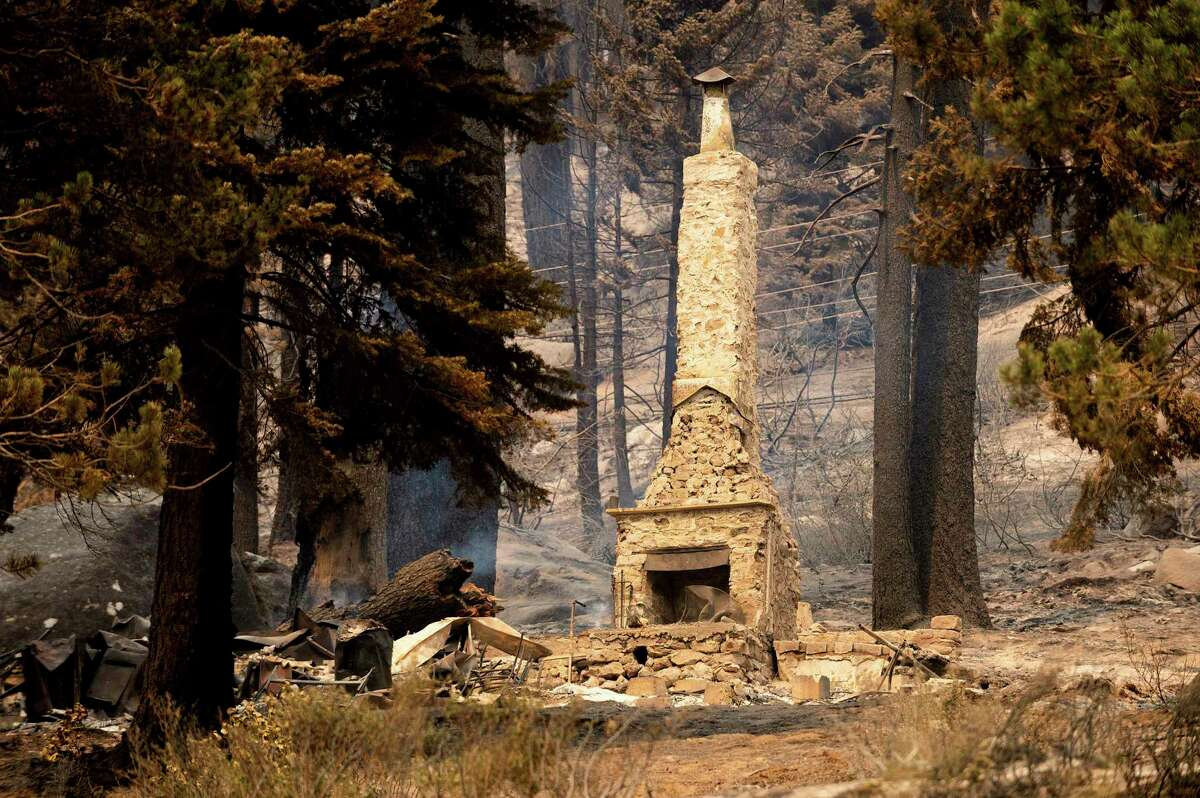 A chimney stands at a home destroyed by the Caldor Fire along Highway 50 in Eldorado National Forest. The forest is among several that remain closed after the National Forest Service reopened most national forests in California at midnight Wednesday after a shutdown due to wildfire risk.