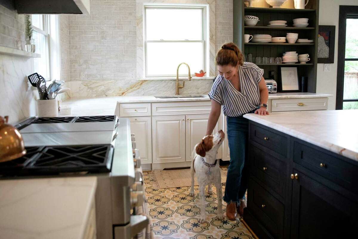 The large, 4-by-6-foot island at the center of the kitchen has a marble countertop and slightly distressed hand-stained maple cabinets below.