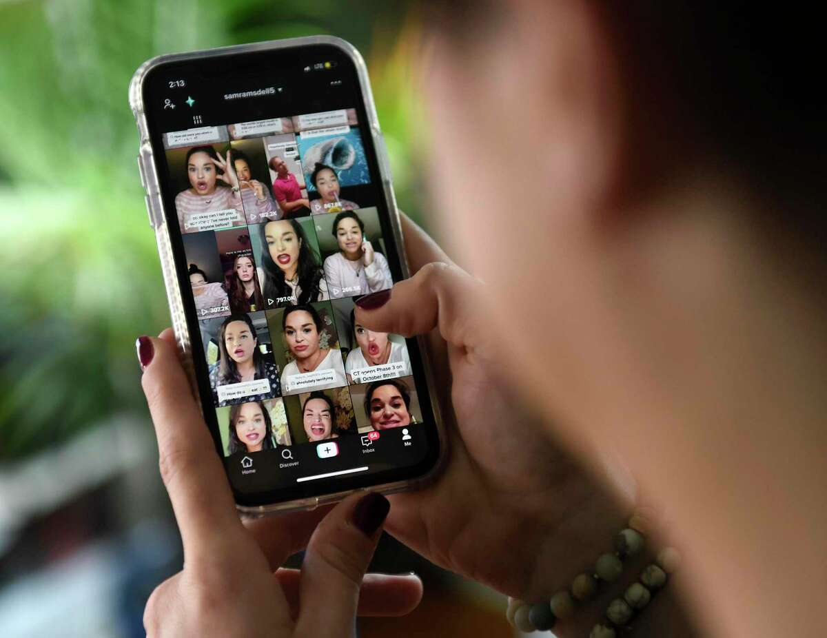 A TikTok star shows her TikTok feed on her phone at her home in Stamford, Conn. Tuesday, Oct. 27, 2020.
