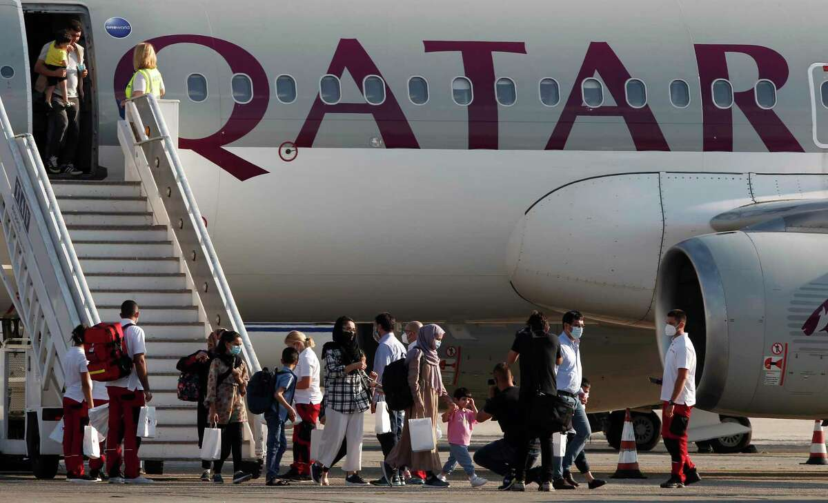 Afghan evacuees disembark the plane and board a bus after landing at Skopje International Airport, North Macedonia, on Wednesday, Sept. 15, 2021. Connecticut Gov. Ned Lamont said the state could get as many as 310 refugees and welcomes them with open arms. (AP Photo/Boris Grdanoski)