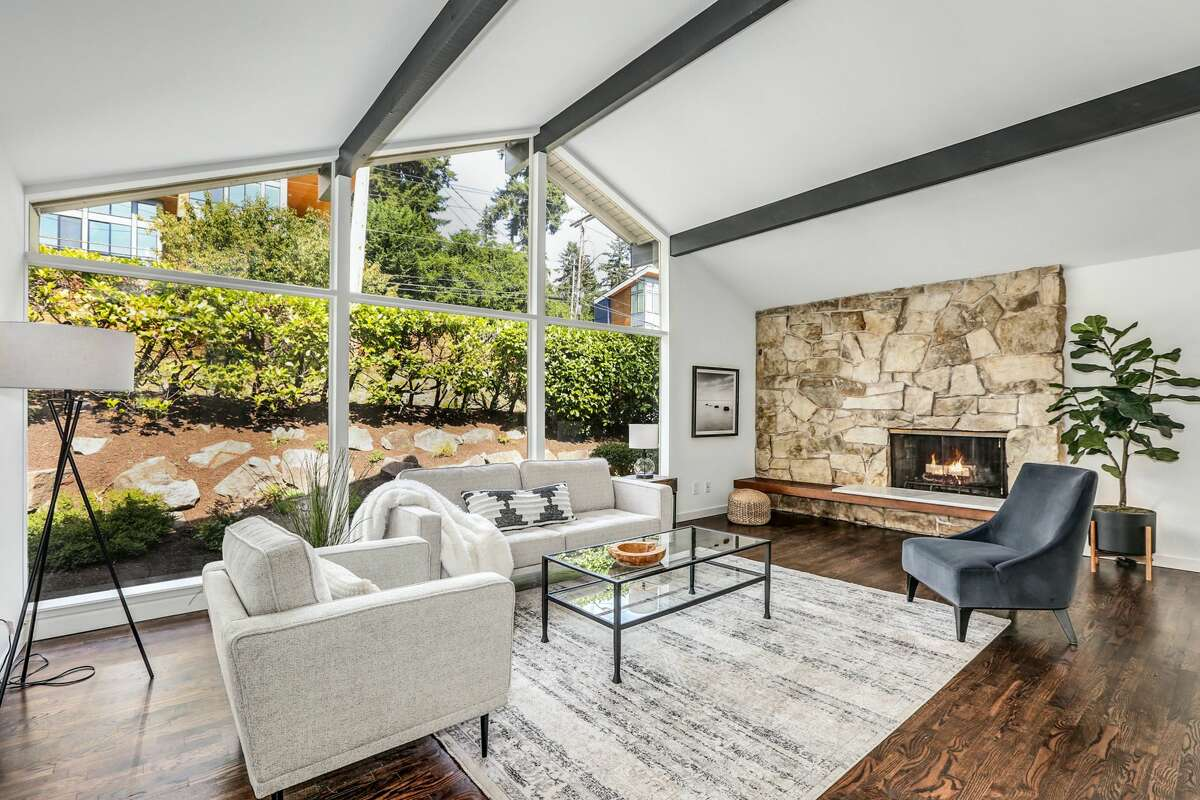 A large fireplace and hearth warm the dramatic angles in the living room.