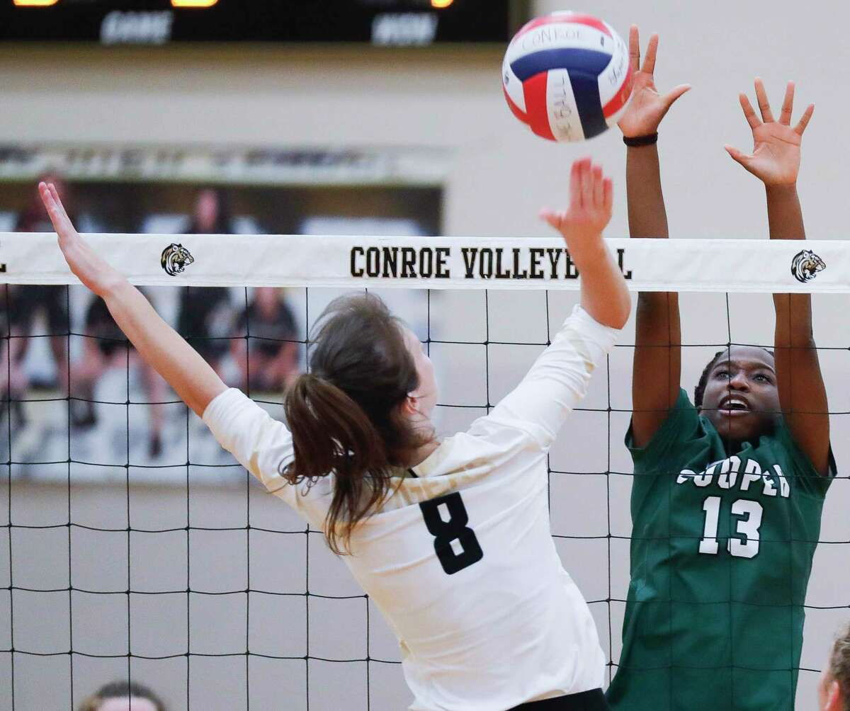 John Cooper middle blocker Onese Ewherido (13) pressures a shot by Conroe middle blocker Brooklyn Spikes (8) during the third set of a non-district high school volleyball match at Conroe High School, Wednesday, Sept. 15, 2021, in Conroe.