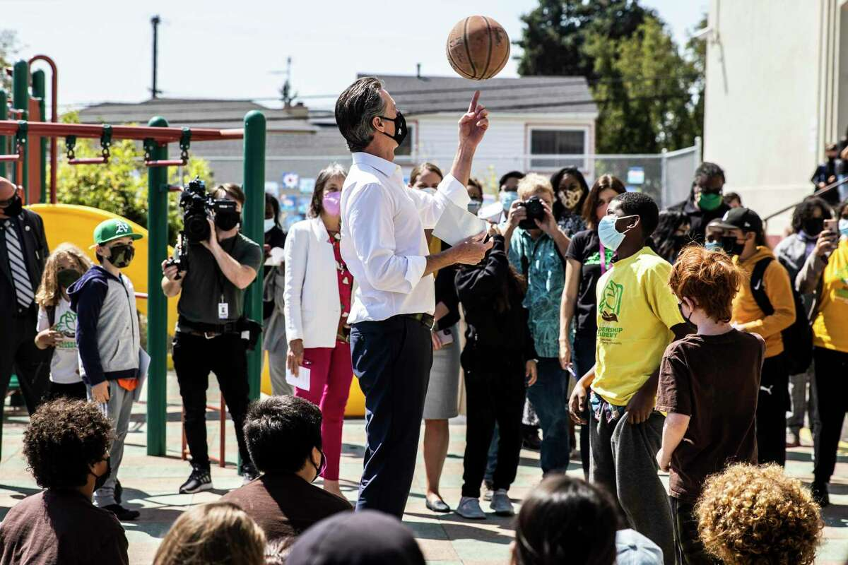 California Governor Gavin Newsom spins a basketball during a visit at Melrose Leadership Academy the day after surviving the gubernatorial recall election in Oakland, California Wednesday, Sept. 15, 2021.