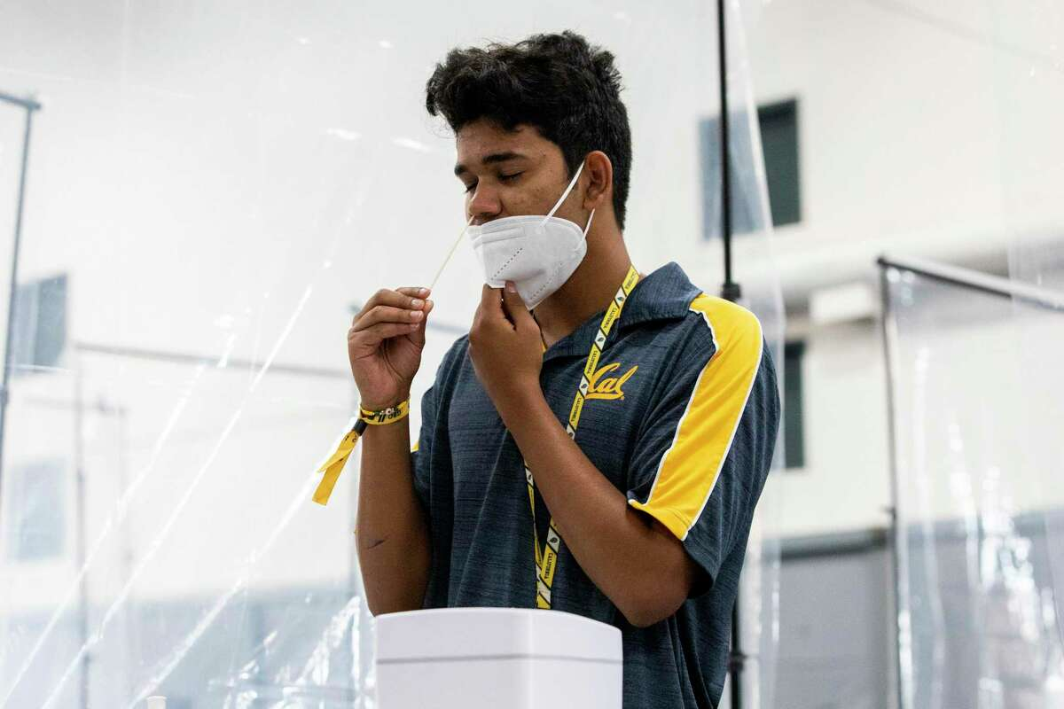 Yash Hande conducts his own COVID-19 test at a mass testing site set up in UC Berkeley's Tang Center on August 23, 2021. Case rates and hospitalizations are down in the Bay Area.