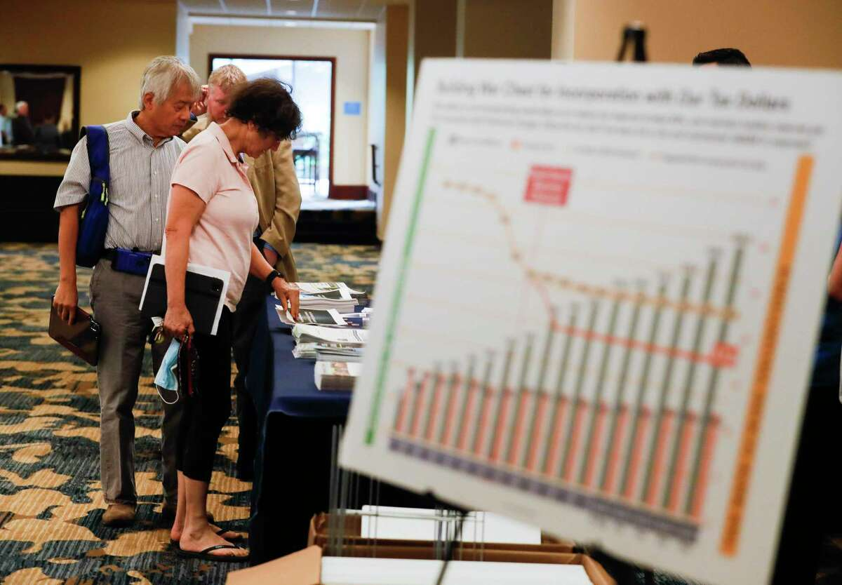Residents pick up information on incorporation before a panel discussion on incorporation of The Woodlands Township, Wednesday, Sept. 15, 2021, in The Woodlands.
