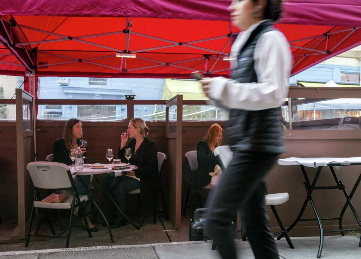 A pedestrian walks by diners at Terzo restaurant, which has been serving meals and drinks to customers at a parklet due to Covid occupancy rules in San Francisco.