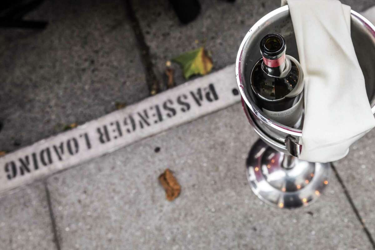 A bottle of wine chills in an ice bucket next to diners at Terzo restaurant where they have been serving meals and drinks to customers at a parklet due to Covid occupancy rules in San Francisco, Calif., on Tuesday, September 14, 2021. California legislators are considering a bill to make permanent the pandemic rules allowing alcohol to be served in parklets and through cocktail delivery.