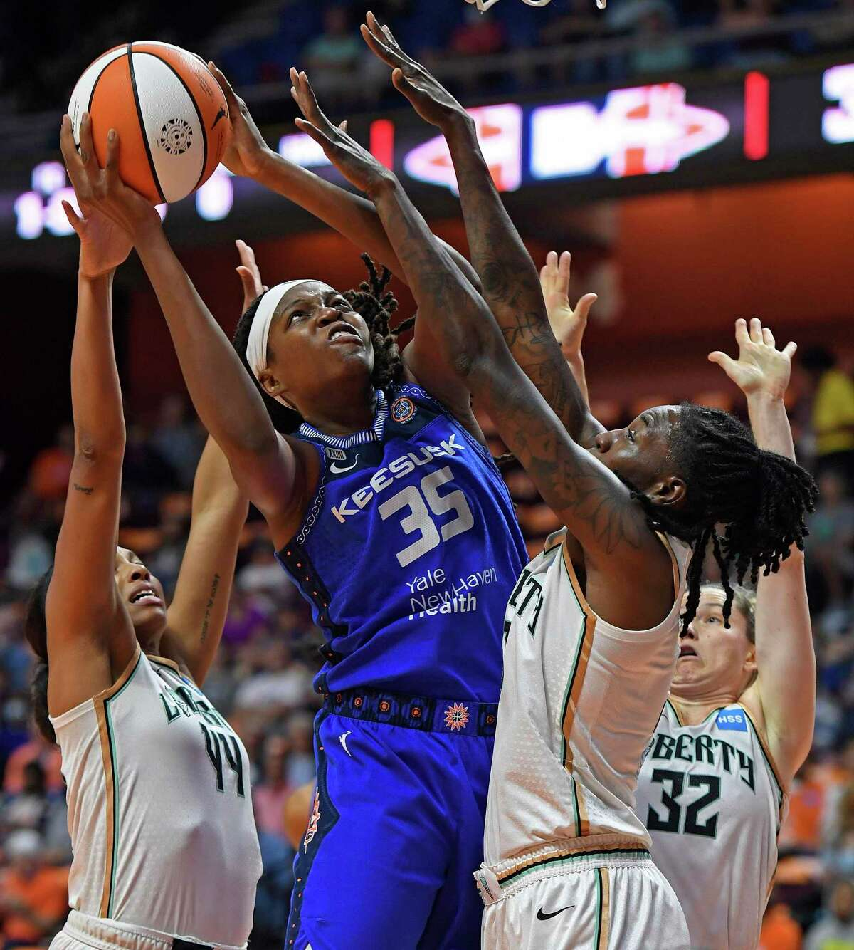 Connecticut Sun forward Jonquel Jones (35) shoots over New York Liberty defenders Betnijah Laney, left, Sami Whitcomb (32) and Natasha Howard during the first half of a WNBA basketball game Wednesday, Sept. 15, 2021, in Uncasville, Conn. (Sean D. Elliot/The Day via AP)