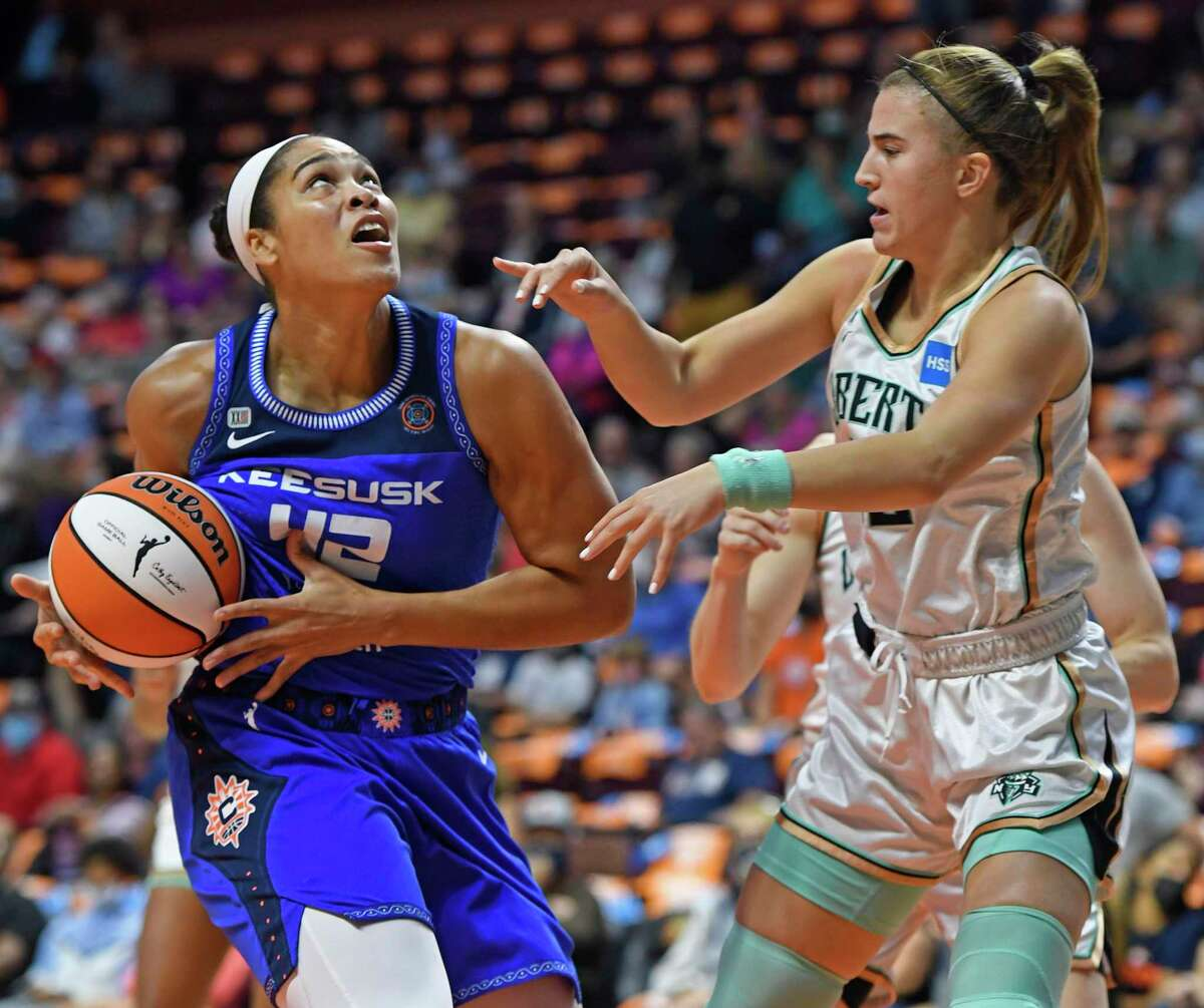 Connecticut Sun center Brionna Jones (42) drives to the basket as New York Liberty guard Sabrina Ionescu defends during the first half of a WNBA basketball game Wednesday, Sept. 15, 2021, in Uncasville, Conn. (Sean D. Elliot/The Day via AP)