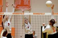 Bridge City's Demi Carter (left) and Caryss Carpenter defend against Orangefield's Kennedi Dubois' spike at the net during their volleyball match-up at Orangefield. Photo made Wednesday, September 15, 2021 Kim Brent/The Enterprise