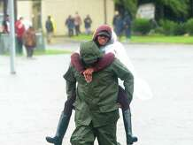 An evacuee gets a piggy back ride through the flooded waters surrounding the Max Bowl, which was converted to a shelter for those displaced by flooding in Port Arthur.  Photo taken Wednesday, August 30, 2017 Kim Brent/The Enterprise