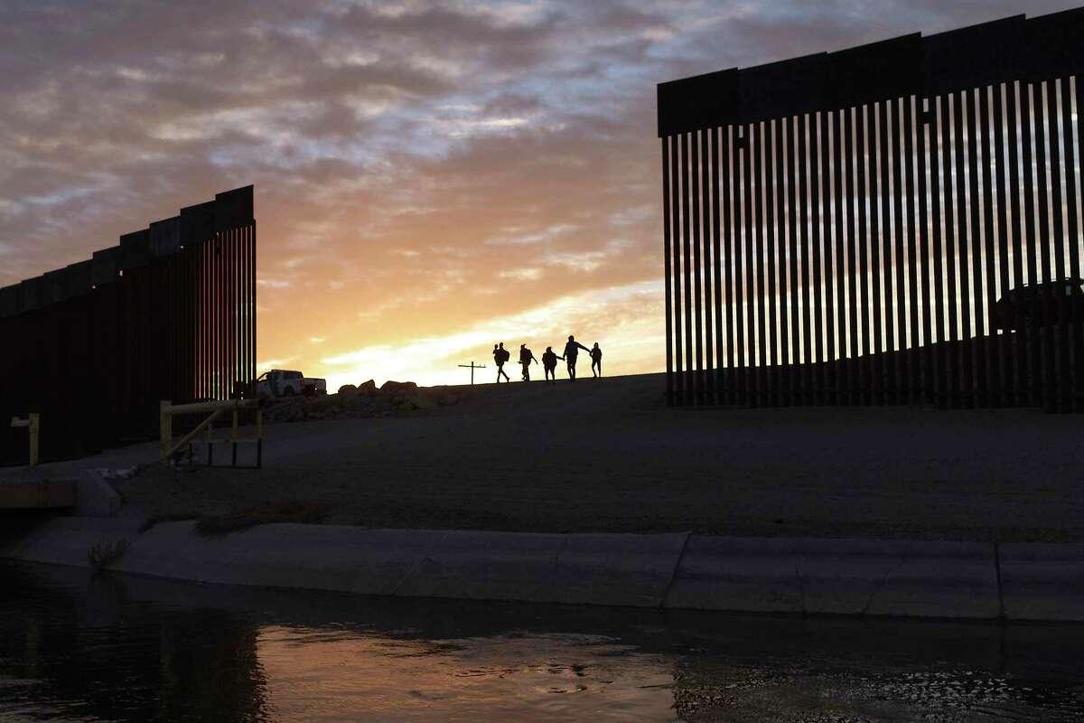 RCHIVO - En esta fotografía de archivo del jueves 10 de junio de 2021, un par de familias migrantes de Brasil pasan a través de un espacio libre en el muro fronterizo para ingresar a Yuma, Arizona, desde México con el fin de solicitar asilo.