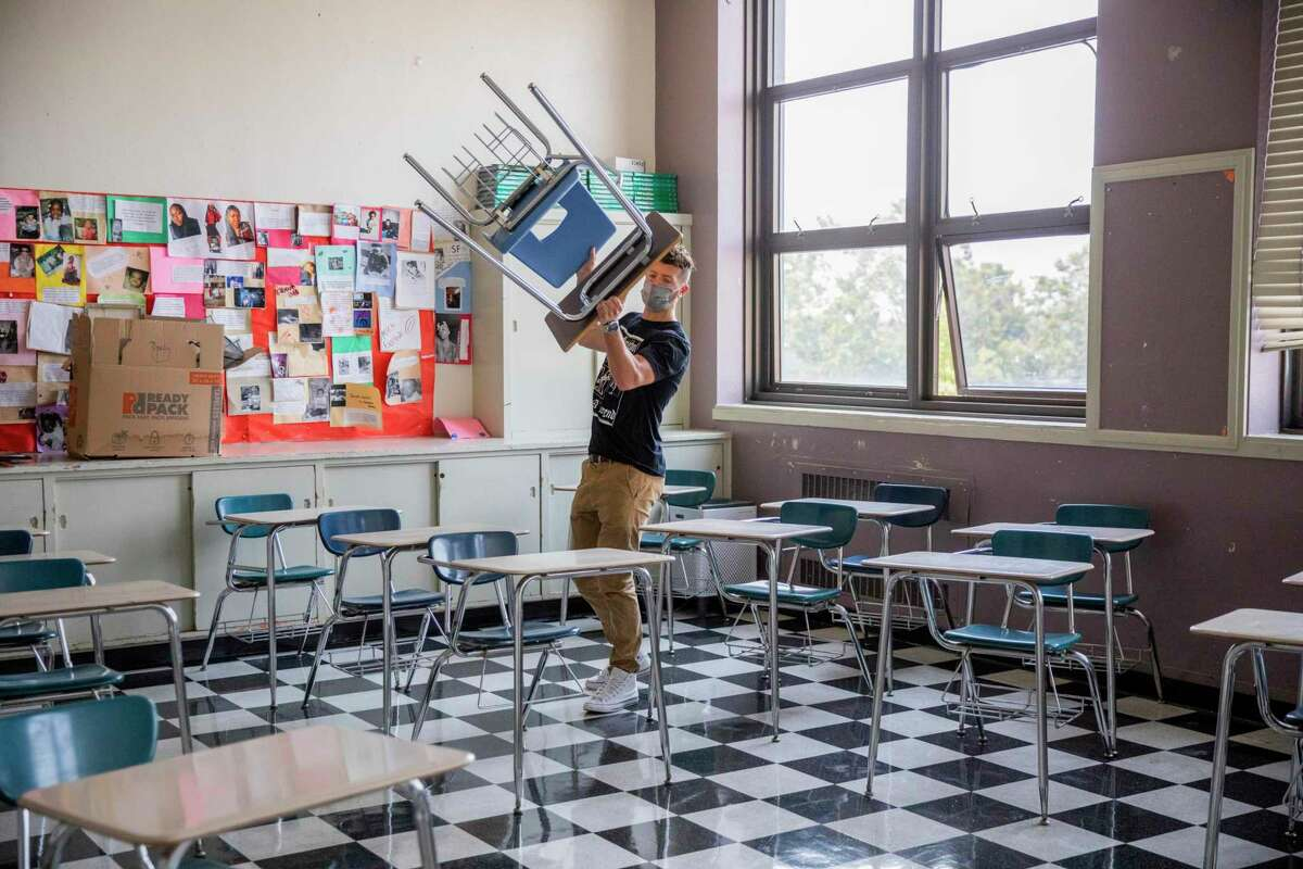 Braden DeWitt begins to arrange desks for physical distancing inside his classroom at McClymonds High School, Friday, Aug. 6, 2021, in Oakland, Calif. DeWitt has taught Spanish to juniors and seniors at the school for the last three years. He prepares to teach in-person at the school on Monday.