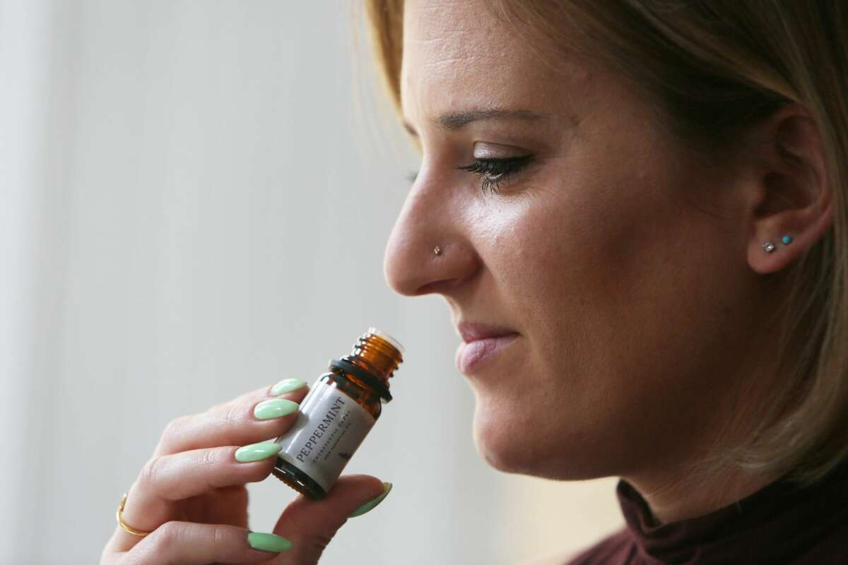 Catherine Berner of San Francisco, who lost her sense of smell when she got COVID-19 in October, smells an essential oil while conducting scent training.